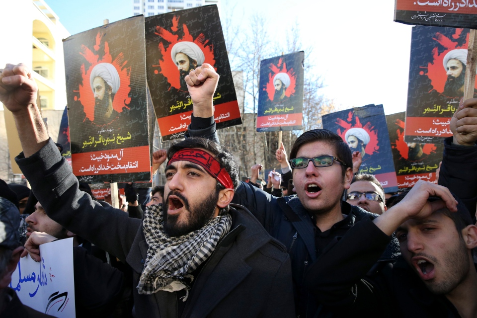 Iranian demonstrators chant slogans during a protest denouncing the execution of Sheikh Nimr al-Nimr, a prominent opposition Shiite cleric in Saudi Arabia, seen in posters, in front of the Saudi Embassy, in Tehran, Sunday, Jan. 3, 2016. (AP / Vahid Salemi)