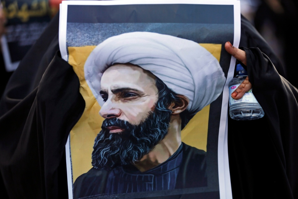 A Bahraini protester holds a picture of Saudi Shiite cleric Sheikh Nimr al-Nimr during a rally denouncing the execution of Shiite cleric Sheikh Nimr al-Nimr by Saudi Arabia, Sunday, Jan. 3, 2016, in Daih, Bahrain. (AP Photo/Hasan Jamali)