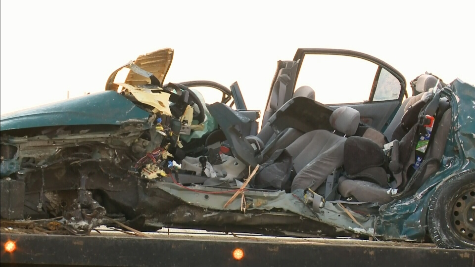 A damaged car is removed from the scene of a fatal Highway 11 crash.