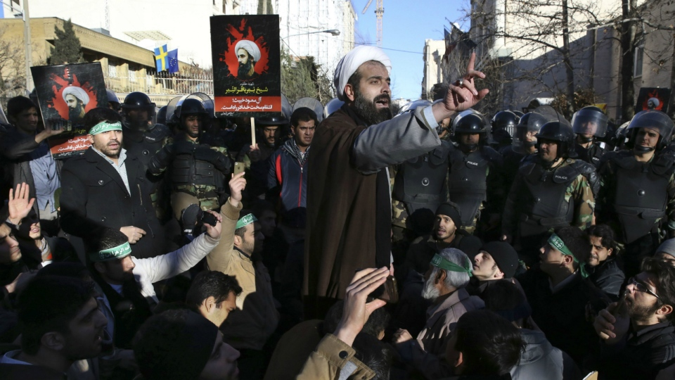Surrounded by policemen, a Muslim cleric addresses a crowd during a demonstration to denounce the execution of Saudi Shiite Sheikh Nimr al-Nimr, seen in poster, in front of the Saudi embassy in Tehran, Iran, Sunday, Jan. 3, 2016. (AP / Vahid Salemi)