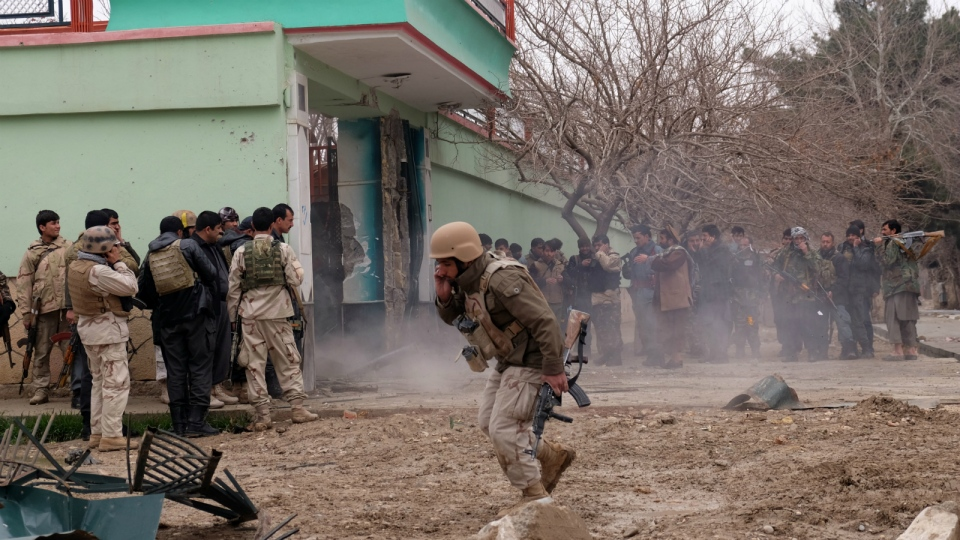 Afghan security forces surround a house which is used by a group of gunmen to attack on the Indian Consulate in Mazar-e-Sharif, capital of northern Balkh province, Afghanistan, Monday, Jan. 4, 2016. (AP / Asghar Normohammadi)