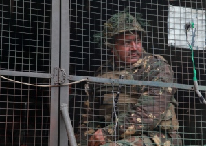 An Indian army soldier looks from inside an army vehicle at the contested Indian air force base in Pathankot, India, Monday, Jan.4, 2016. (AP Photo / Channi Anand)