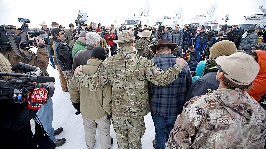 Members of the group occupying the Malheur National Wildlife Refuge headquarters hug after Ammon Bundy, center, left, one of the sons of Nevada rancher Cliven Bundy, spoke with reporters during a news conference Monday, Jan. 4, 2016, near Burns, Ore. (AP / Rick Bowmer)
