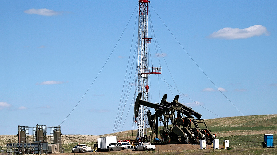 An oil rig and pumps in Watford City, N.D. June 12, 2014. (AP / Charles Rex Arbogast)