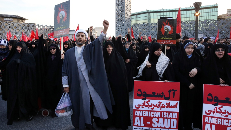 A Muslim cleric chants slogans alongside women in a rally to protest the execution by Saudi Arabia last week of Sheikh Nimr al-Nimr, a prominent opposition Saudi Shiite cleric, in Tehran, Iran, Monday, Jan. 4, 2016. (AP / Vahid Salemi)