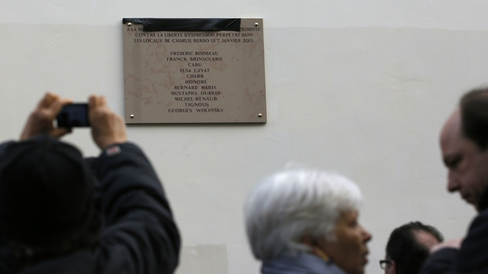 People picture a plaque unveiled earlier by French President Francois Hollande outside satirical newspaper Charlie Hebdo former office in Paris on Tuesday, Jan. 5, 2016. (AP / Christophe Ena)