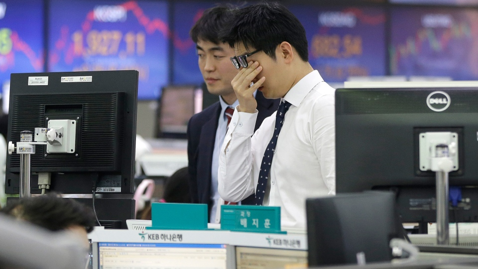 A currency trader rubs his eyes at the foreign exchange dealing room of the KEB Hana Bank headquarters in Seoul, South Korea, Tuesday, Jan. 5, 2016. (AP / Ahn Young-joon)
