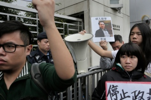 In this Sunday, Jan. 3, 2016, file photo, a protester holds a photo of missing bookseller Lee Bo during a protest outside the Liaison of the Central People's Government in Hong Kong. (AP Photo/Vincent Yu, File)