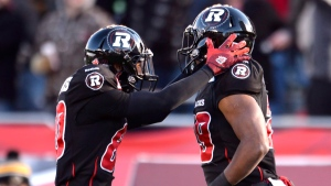 Ottawa Redblacks's Chris Williams, left, and William Powell celebrate Powell's touchdown against the Hamilton Tiger-Cats during first half action in the CFL East Division final in Ottawa, Sunday November 22, 2015. (Adrian Wyld/The Canadian Press)