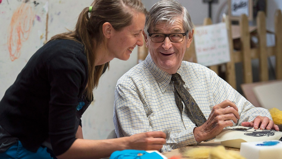 Erin Laende of the Art Gallery of Nova Scotia and Jack Hallisey, who lives with Alzheimer's disease, work on an art project as the province's first dementia strategy is announced in the same room in Halifax on Monday, June 23, 2015. (Andrew Vaughan / THE CANADIAN PRESS)