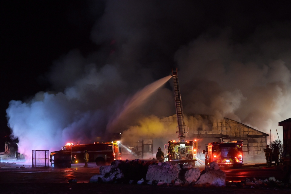 Firefighters work to bring a blaze under control at the Classy Lane Stables, in Puslinch, Ont., on Jan. 5, 2015. (Andrew Collins  / THE CANADIAN PRESS)