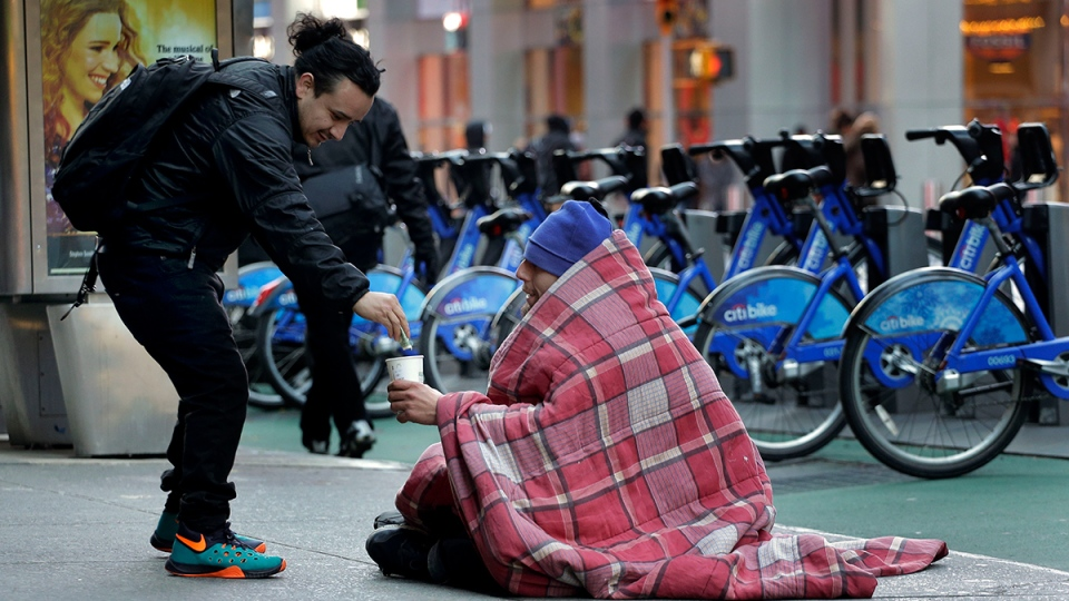 A pedestrian drops money in a cup for a homeless man near Times Square, Monday, Jan. 4, 2016, in New York. (AP / Julie Jacobson)