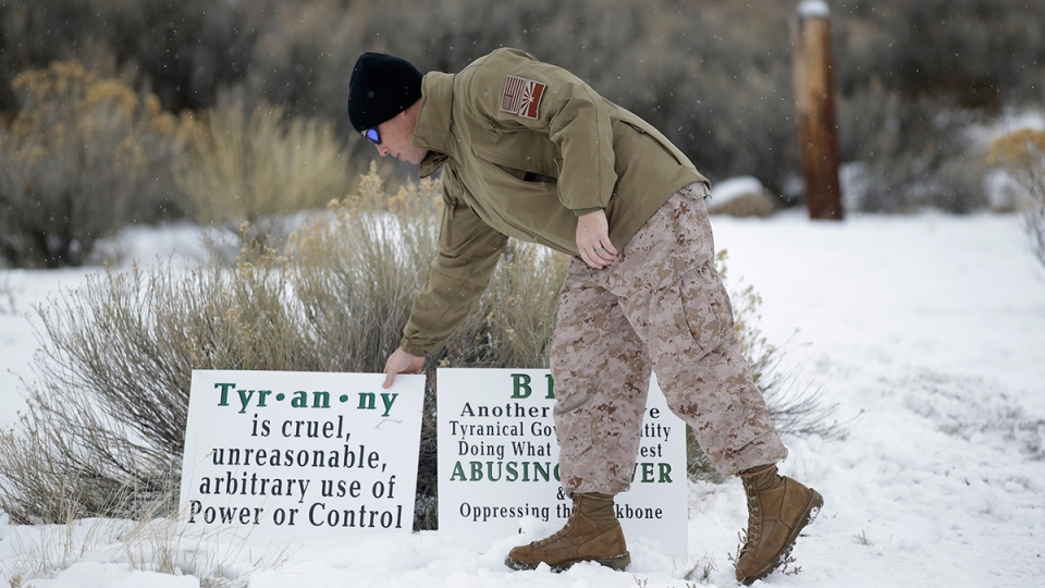 Jon Ritzheimer, of Arizona, a member of the group occupying the Malheur National Wildlife Refuge headquarters, adjust a sign, near Burns, Ore., Tuesday, Jan. 5, 2016. (AP / Rick Bowmer)