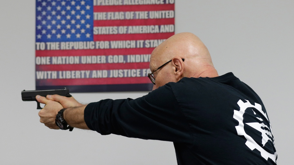 Mike Weinstein, director of training and security at the National Armory gun store and gun range, shows how to safely fire a Glock 9mm hand gun during a Concealed Weapons Permit class on Tuesday, Jan. 5, 2016, in Pompano Beach, Fla. (AP / Lynne Sladky)