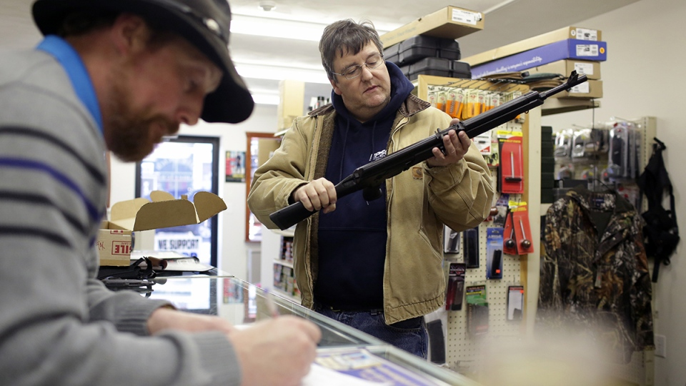 Joe McGrew, of Lake Ariel, Pa., inspects his new Saiga AK-47 style rifle as Rich Johnson, left, owner of Big Rich American Sports Shop processes his background check in Scranton, Pa., Tuesday, Jan. 5, 2016. (Jake Danna Stevens / The Times & Tribune via AP)