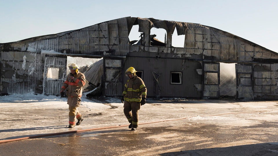 Firefighters walk past a barn that was destroyed by a fire at the Classy Lanes Stables in Puslinch, Ont., on Tuesday, Jan. 5, 2016. (Hannah Yoon / THE CANADIAN PRESS)