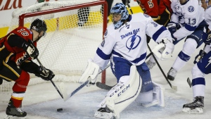 Tampa Bay Lightning goalie Ben Bishop, centre, looks back as Calgary Flames' Matt Stajan scores during first period NHL hockey action in Calgary, Tuesday, Jan. 5, 2016. (Jeff McIntosh / THE CANADIAN PRESS)