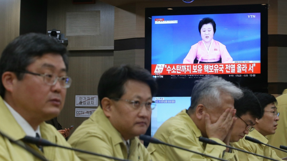 South Korean Foreign Ministry officials attend an emergency meeting as a TV news program showing North Korea's announcement at the ministry in Seoul, South Korea, Wednesday, Jan. 6, 2016. (Kim Ju-sung / Yonhap)