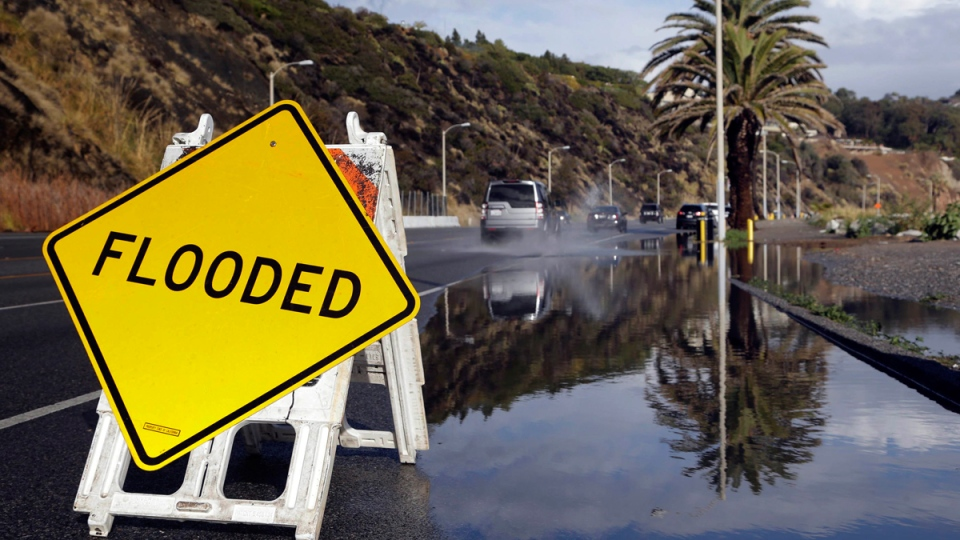 A sign warning of flooded road is posted along the Pacific Coast Highway in Malibu, Calif., on Jan. 5, 2016. (Nick Ut / AP)