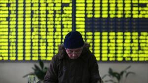 An investor pauses near a display board showing stock prices at a brokerage house in Jiujiang, China, on Monday, Jan. 4, 2016. (Chinatopix Via AP)