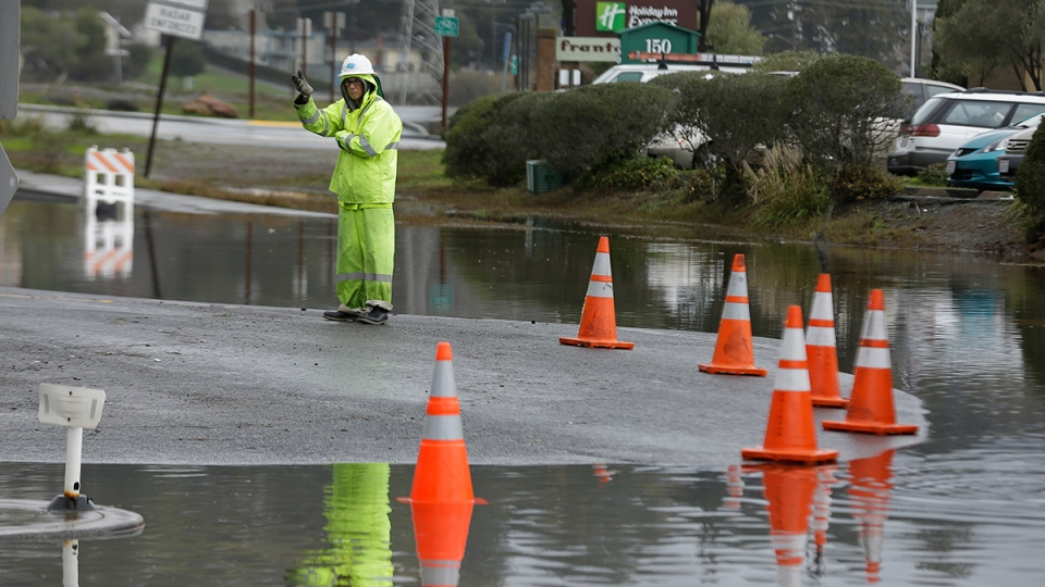 A Caltrans worker directs traffic around a flooded roadway Wednesday, Jan. 6, 2016, in Mill Valley, Calif. (AP / Eric Risberg)