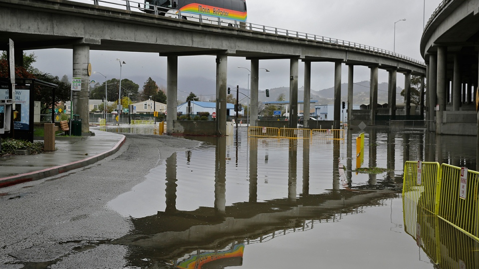 An airport bus comes down an offramp over a flooded commuter lot, in Mill Valley, Calif., Wednesday, Jan. 6, 2016. (AP / Eric Risberg)