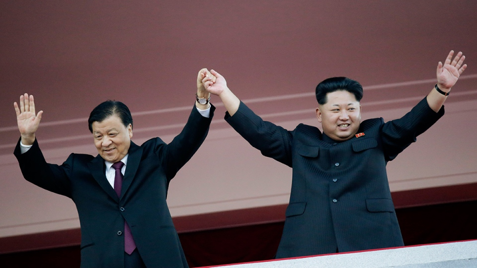North Korean leader Kim Jong Un, right, joins hands and waves with visiting Chinese official Liu Yunshan, the Communist Party's fifth-ranking leader, during a parade in Pyongyang, North Korea, Oct. 10, 2015. (AP / Wong Maye-E)