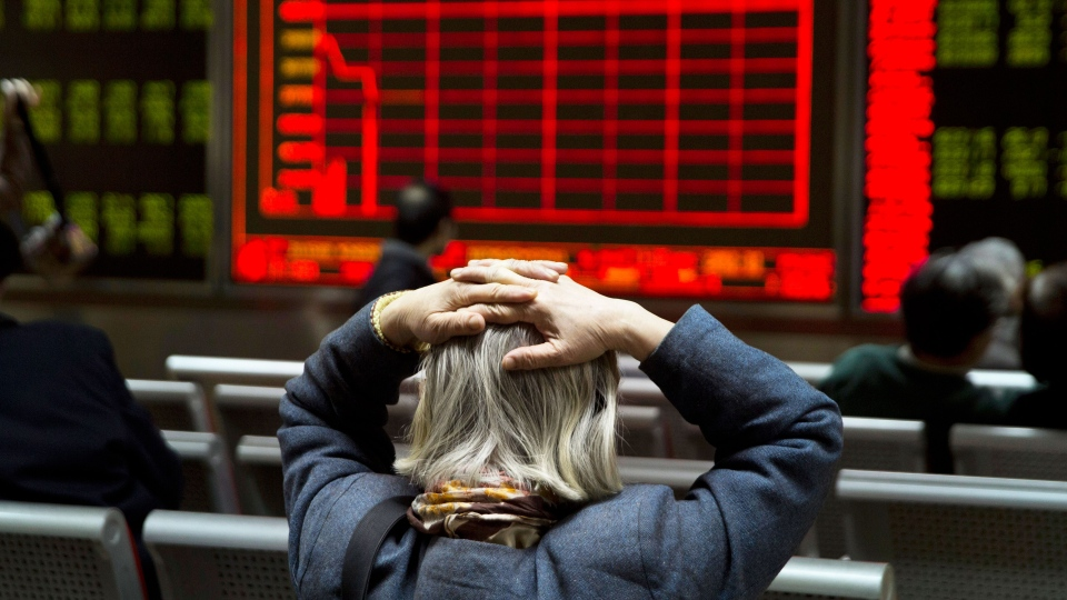A woman reacts near a display board showing the plunge in the Shanghai Composite Index at a brokerage in Beijing, China, Thursday, Jan. 7, 2016.  (AP / Ng Han Guan)
