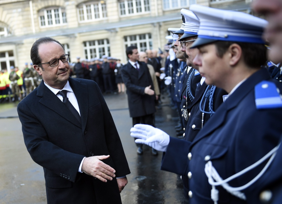 French President Francois Hollande shakes hands to police officers at the Paris' police headquarters, Thursday Jan. 7, 2016, one year after the attack targeting the French satirical newspaper Charlie Hebdo. (Martin Bureau, Pool Photo via AP)