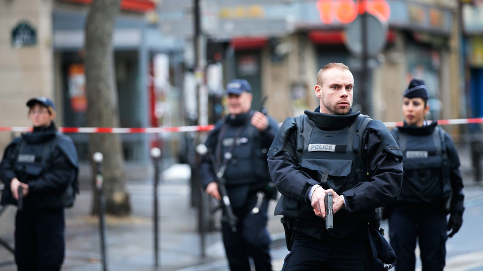 Police officers secure the perimeter near the scene of a fatal shooting which took place at a police station in Paris, Wednesday, Jan. 7, 2016.  (AP / Christophe Ena)
