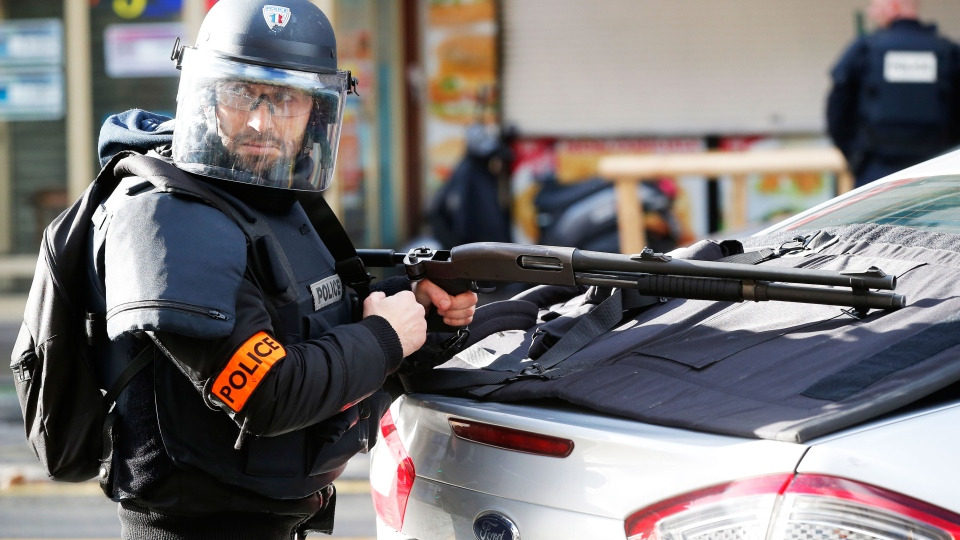 A police officer takes position after a fatal shooting which took place at a police station in Paris, Thursday, Jan. 7, 2016. (AP / Michel Euler)