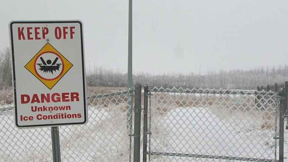 A sign and fence are in place as measures to keep people off the ice at Poplar Lake, in Edmonton, Alta.