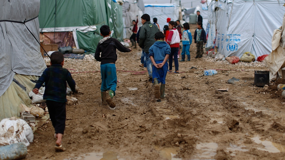 Syrian refugee children walk in mud from the heavy rain at a refugee camp in the town of Hosh Hareem, in the Bekaa valley, east Lebanon, Monday, Jan. 4, 2016. (AP / Hassan Ammar)