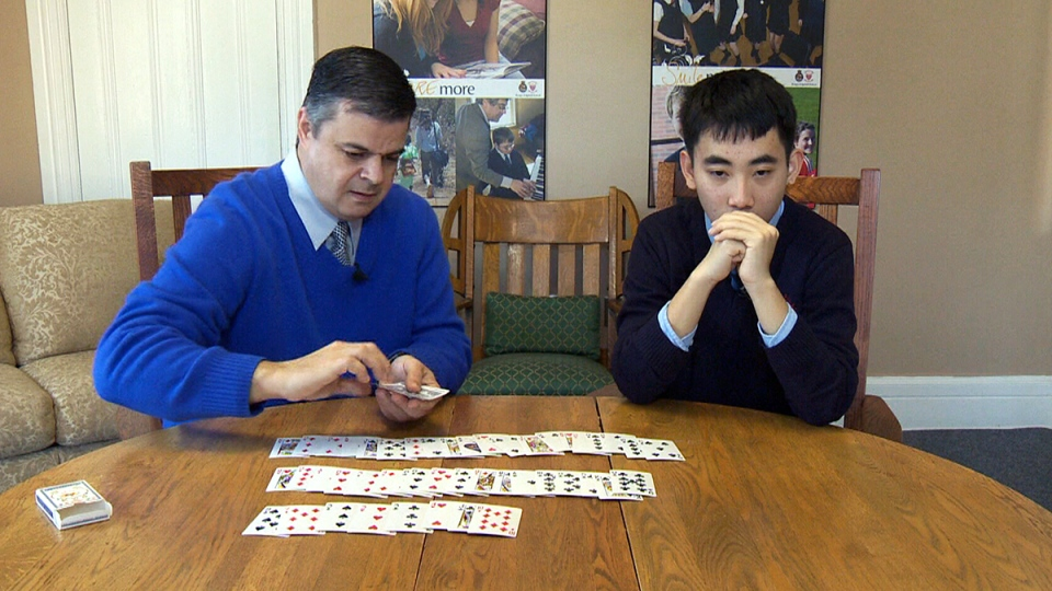 King's-Edgehill School director of admissions Chris Strickey flips over playing cards as Evan Xie names them in the correct order, from memory, in Windsor, N.S.