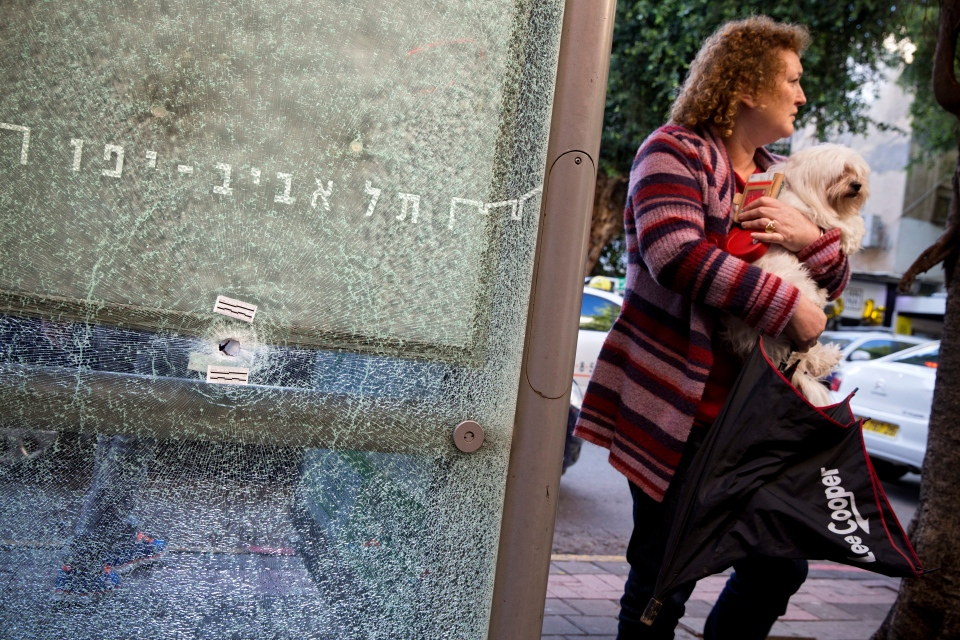 In this Saturday, Jan. 2, 2016, file photo, an Israeli woman holds her dog next to a bus station shattered by bullets at the scene of a deadly shooting attack, in Tel Aviv, Israel. (AP Photo/Oded Balilty, File)