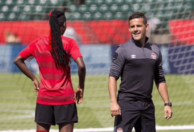 In this June 5, 2015 file photo, Canada's head coach John Herdman and Kadeisha Buchanan chat during a practice session in Edmonton, Alta. (Jason Franson / THE CANADIAN PRESS)