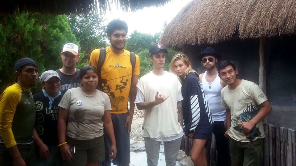 In this Tuesday, Jan. 5, 2016 handout photo provided by the press office for All Tour Native Expeditions, Justin Bieber and unidentified members of his entourage, pose for a photo with Jungla Maya Park employees, in a part of Mexico's Riviera Maya, located between Tulum and Xel-Ha Park.