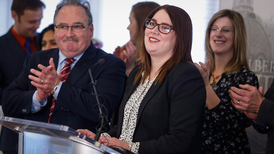 Alberta NDP MLA Deborah Drever, centre, is welcomed back into the NDP caucus by cabinet minister Brian Mason, left, at a news conference in Calgary, Friday, Jan. 8, 2016. (Jeff McIntosh / THE CANADIAN PRESS)