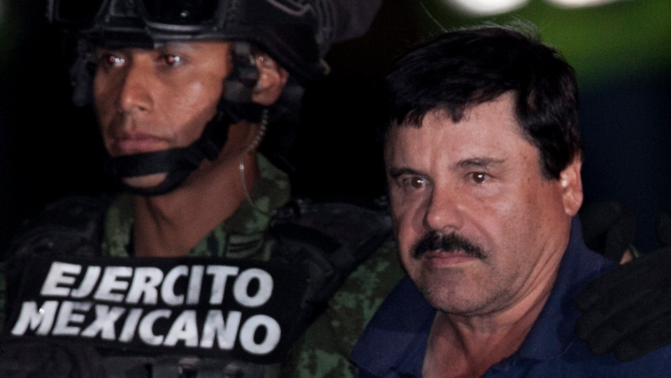 Mexican drug lord Joaquin 'El Chapo' Guzman, right, is escorted by soldiers and marines to a waiting helicopter, at a federal hangar in Mexico City, Friday, Jan. 8, 2016. (AP/Marco Ugarte)