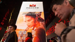 """People walk past a poster for the new """"Star Wars"""" movie at a movie theater in Beijing, Saturday, Jan. 9, 2016. (AP / Mark Schiefelbein)"""