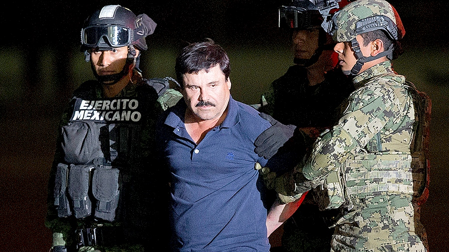 Joaquin 'El Chapo' Guzman is escorted to a helicopter in handcuffs by Mexican soldiers and marines at a federal hangar in Mexico City, Mexico, Friday, Jan. 8, 2016. (AP / Eduardo Verdugo)