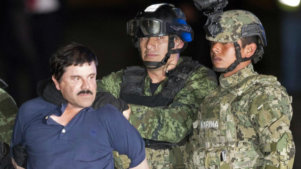 Joaquin 'El Chapo' Guzman is made to face the press as he's escorted to a helicopter in handcuffs by soldiers and marines at a federal hangar in Mexico City on Friday, Jan. 8, 2016 (AP / Eduardo Verdugo)