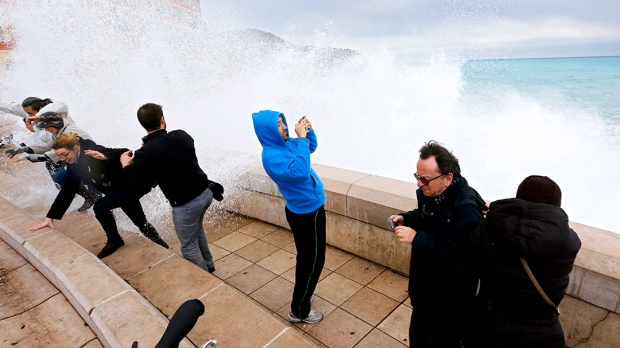 People run away from a wave of Mediterranean sea during a high tide in Nice, southeastern France, Monday, Jan. 11, 2016. (AP / Lionel Cironneau)
