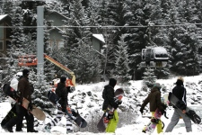Snowboarders pass a gondola car suspended over a creek due to a damaged tower at Blackcomb Mountain in Whistler, B.C., on Wednesday Dec. 17, 2008. (Darryl Dyck / THE CANADIAN PRESS)