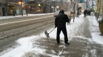 A man clears snow away from a building on Queen Street in downtown Toronto Tuesday January 12, 2016. (Joshua Freeman /CP24)