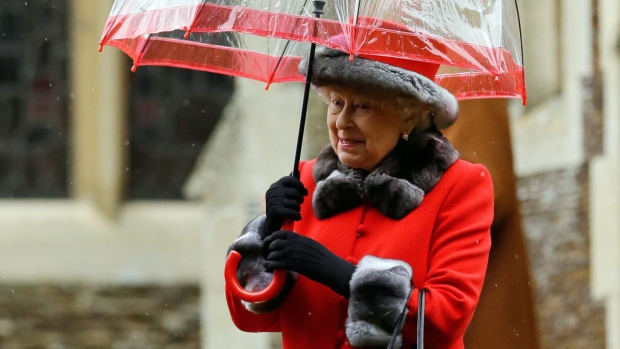 Britain's Queen Elizabeth II shelters under an umbrella as she leaves, after attending the British royal family's traditional Christmas Day church service at St. Mary Magdalene Church in Sandringham, England, Friday, Dec. 25, 2015. (AP / Matt Dunham)