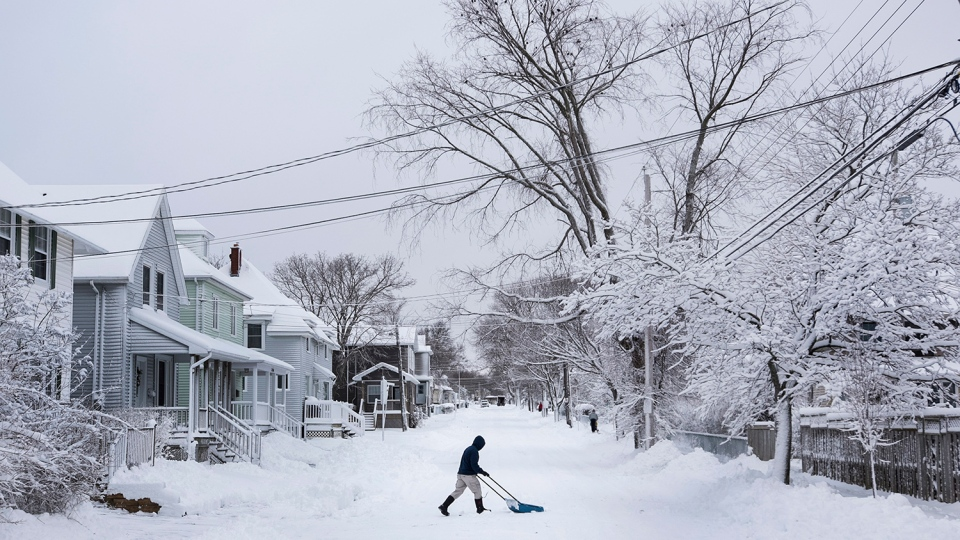 A man clears snow from the middle of the street during a snow storm in Halifax, N.S. on Wednesday, January 13, 2016. (Darren Calabrese / THE CANADIAN PRESS)