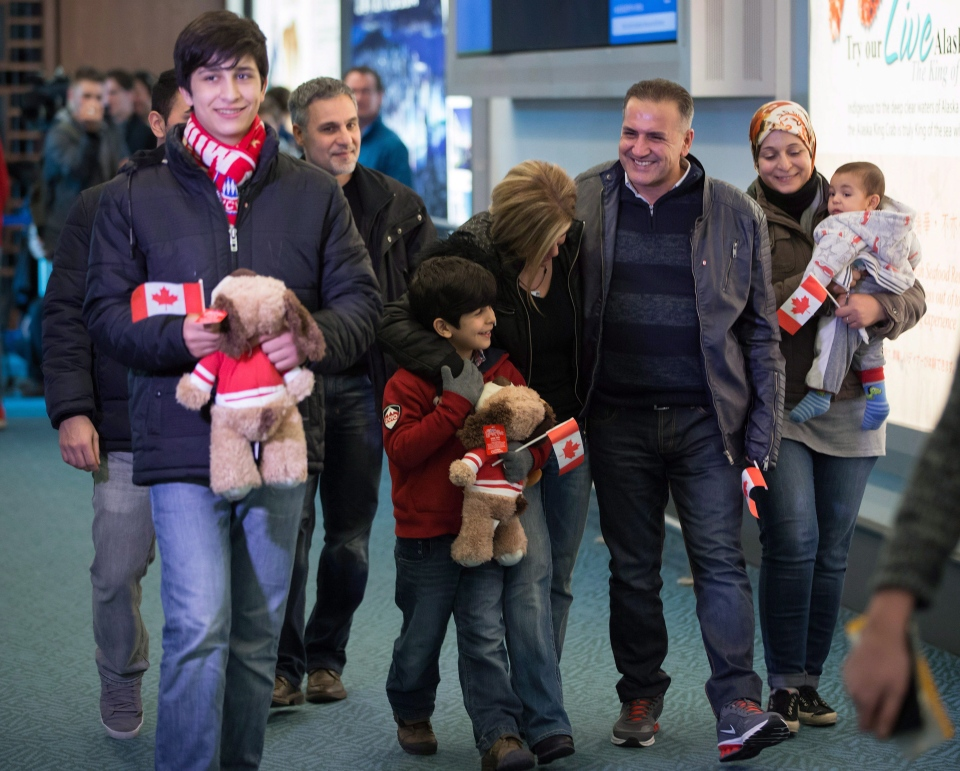 Syrian refugee Mohammad Kurdi, third right, smiles while walking with his sister Tima Kurdi, centre, who lives in the Vancouver area, his wife Ghousun Kurdi, holding their 5-month-old son Sherwan Kurdi, right, and sons Shergo, 14, left, and Rezan, 8, centre left, after arriving at Vancouver International Airport in Richmond, B.C., on Monday, Dec. 28, 2015. (Darryl Dyck / THE CANADIAN PRESS)
