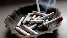 A cigarette burns in an ashtray