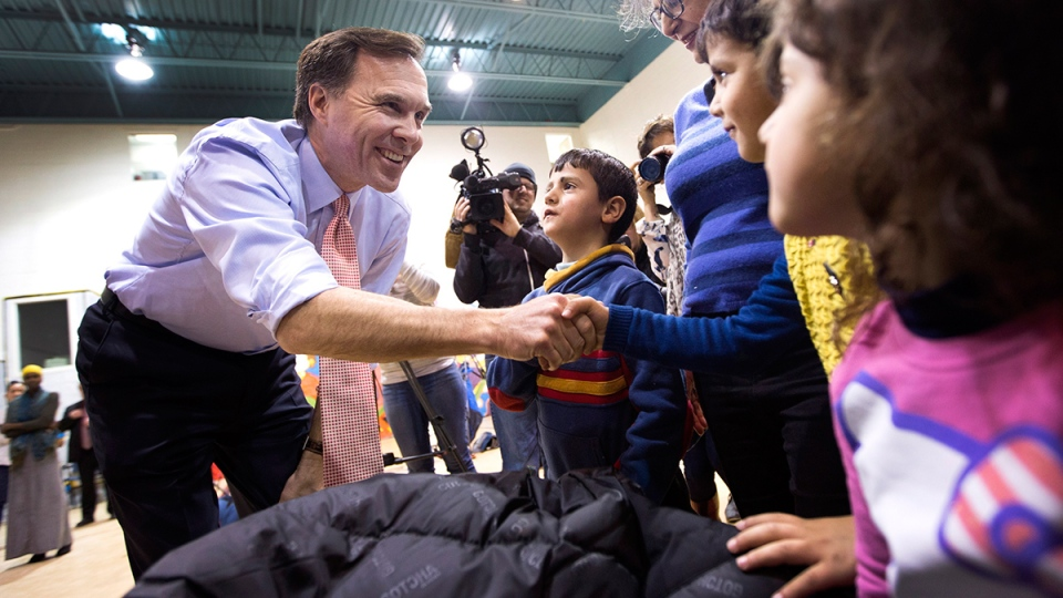 Finance Minister Bill Morneau says hello to three siblings from Syria at Central Neighbourhood House, a Syrian Refugee Welcome Centre in Toronto on Wednesday, Jan. 13, 2016. (Peter Power / THE CANADIAN PRESS)